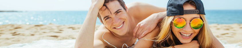 Man and woman lie on beach sharing a pair of headphones